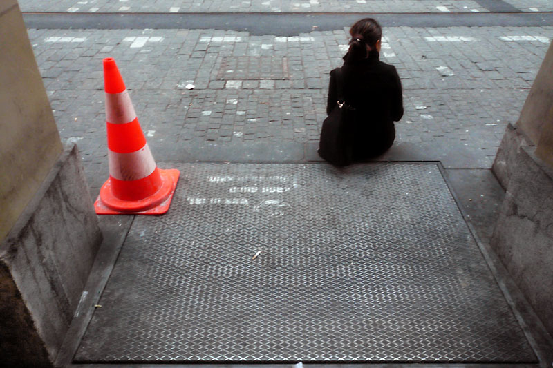 Traffic cone with seated woman