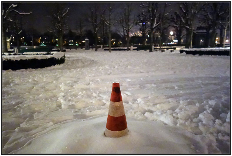 Traffic cone in snow at night