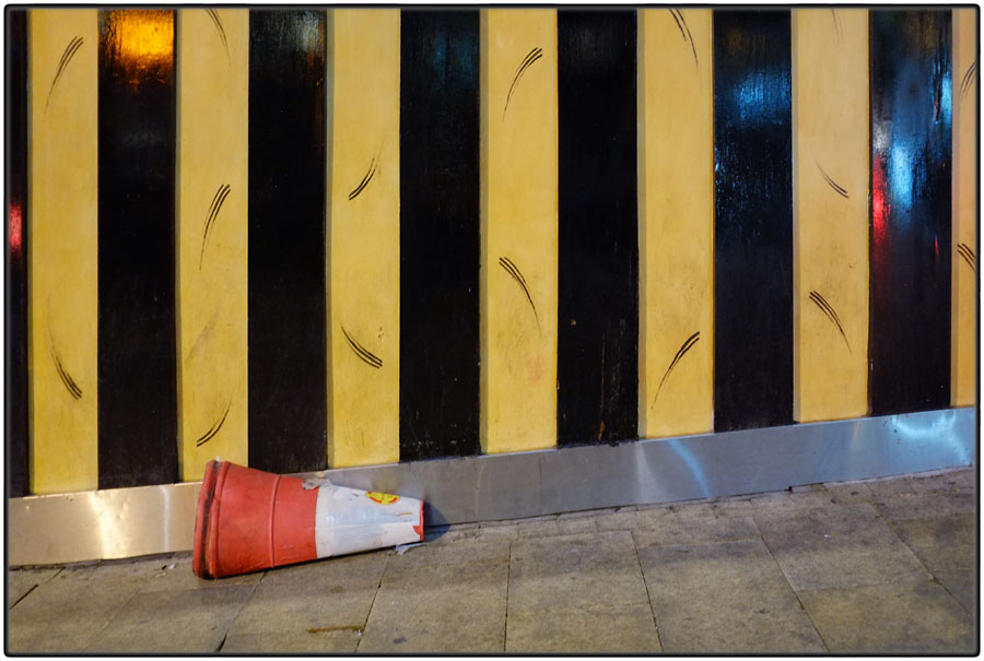 Broken cone in front of black and yellow striped wall