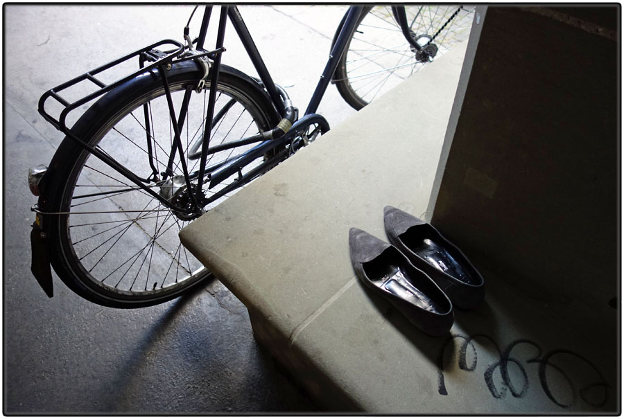 Discarded pointy shoes and bike